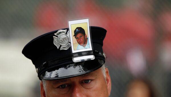 Пожарный с фотографией жертвы теракта 11 сентября 2001 года в Нью-Йорке на церемонии по случаю 10-й годовщины с момента трагедии