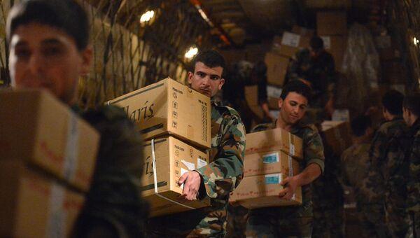 Сирийские военнослужащие разгружают коробки с гуманитарной помощью из России для народа Сирии. Архивное фото