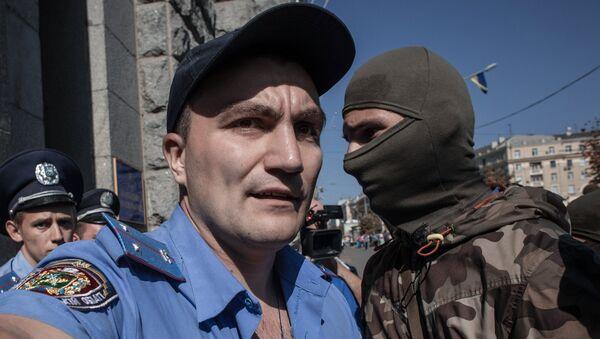 Протестующий и сотрудники правоохранительных органов у здания городского совета Харькова