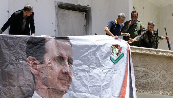 Бойцы Национальных сил обороны Сирии вешают портрет Башара Асада в городе Маалула