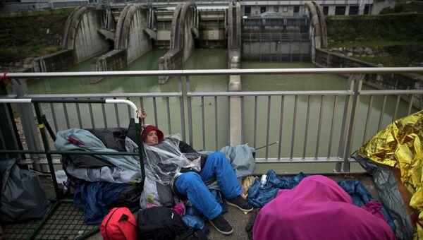 Мигрант из Сирии ждет регистрации и транспортировки в приют для беженцев в городе Фрайлассинг, Германия