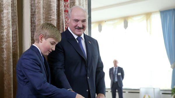 Президент Белоруссии Александр Лукашенко с сыном Николаем на избирательном участке №1 Центрального района Минска