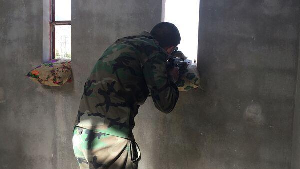 Сирийский военный ведет огонь по позициям боевиков. Архивное фото
