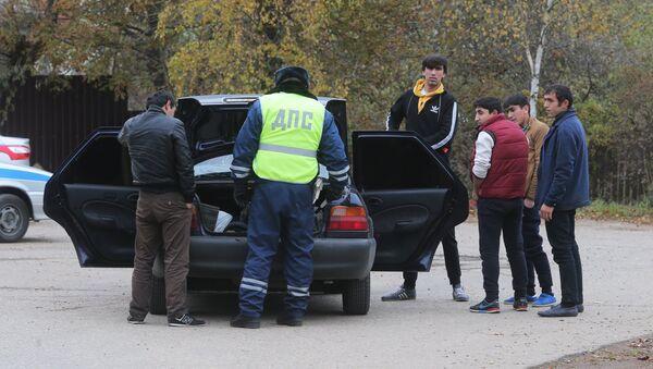 Сотрудник ДПС досматривает машину автовладельца на одной из улиц деревни Тимошкино