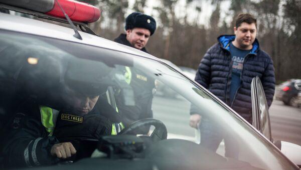 Сотрудник ГИБДД проверяет документы у водителя в рамках рейда скрытых патрулей ДПС в Москве. Архивное фото