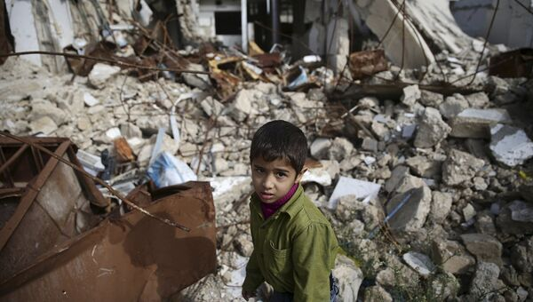 Мальчик среди разрушенных зданий в городе Дума, Дамаск. Сирия, ноябрь 2015