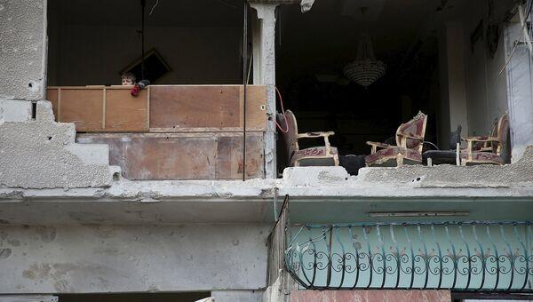 Мальчик выглядывает из разрушенного дома в городе Дума, Дамаск. Сирия, ноябрь 2015
