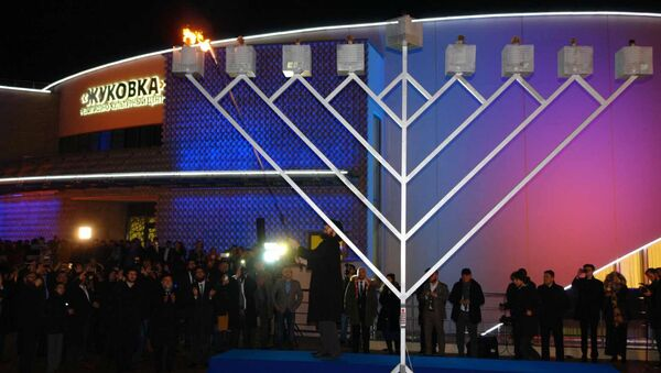 Раввин Ави Гейч зажигает первую свечу Хануки в открывшемся в воскресенье еврейском общинном центре Жуковка в Подмосковье