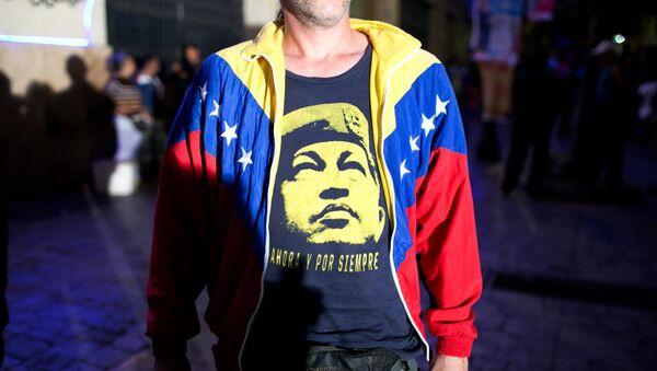 Сторонник правящей партии с портретом Уго Чавеса на футболке в ожидании результатов голосования на парламентских выборах в Каракасе, Венесуэла