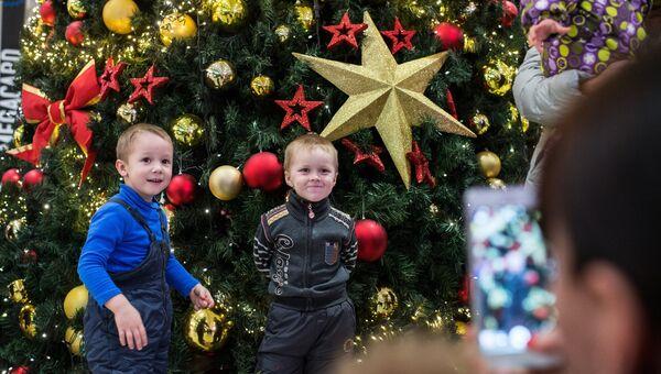 Дети фотографируются у новогодней ёлки. Архивное фото