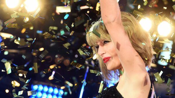 Американская кантри-поп-исполнительница Тейлор Свифт во время празднования Нового года на Таймс-сквер в Нью-Йорке. 2014 год