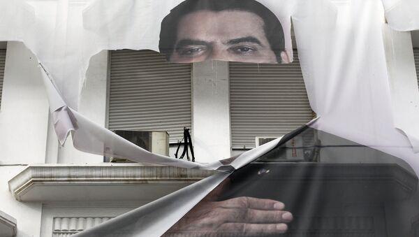 Порванный плакат бывшего президента Туниса Зин аль-Абидин Бен Али. 16 января 2011 года