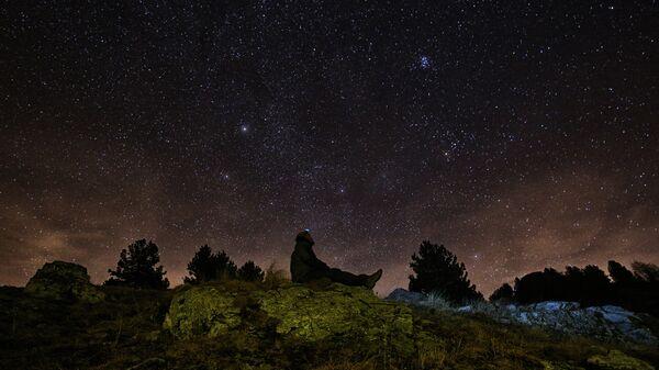 Человек наблюдает метеоритный дождь Геминиды на севере Италии