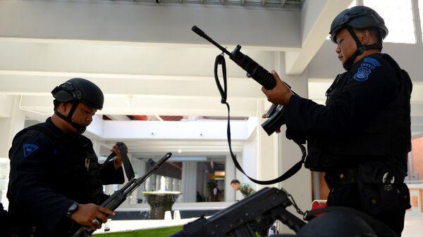 Сотрудники правоохранительных органов Индонезии проверяют оружие перед выходом на службу. Архивное фото