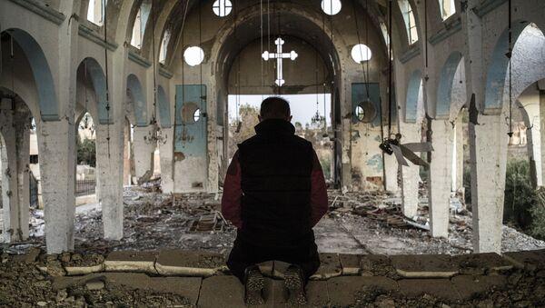 Житель одной из деревень в провинции Эль-Хасаке на северо-востоке Сирии молится в храме Святого Георгия, уничтоженного боевиками ИГ. Архивное фото