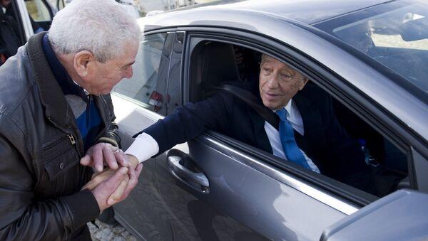 Кандидат в президенты Португалии Марселу Ребелу ди Соза приветствует избирателей после голосования. 24 января 2016