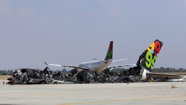 Сгоревший в результате обстрела пассажирский лайнер в аэропорту Триполи, Ливия. Август 2011