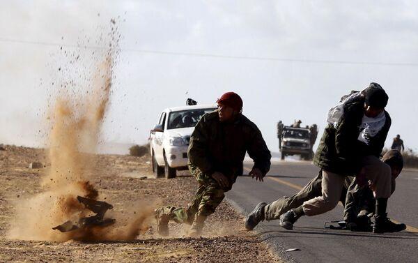 Бойцы оппозиции под обстрелом войск Каддафи у города  Бин-Джавад, Ливия. Март 2011