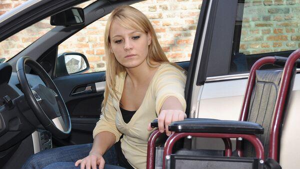 Женщина-инвалид садится за руль автомобиля. Архивное фото