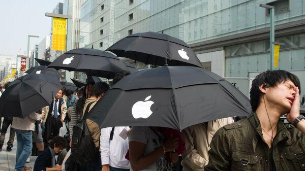 Люди стоят в очереди у Apple Store в Токио в ожидании начала продаж iPhone 4S