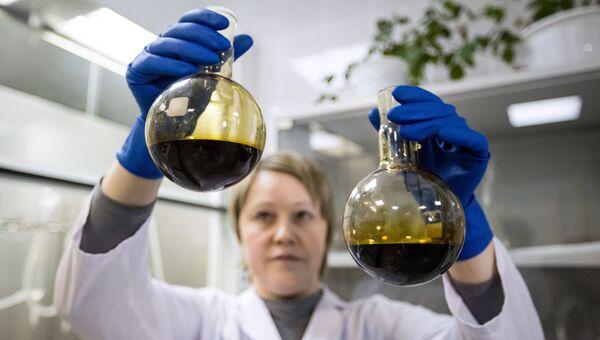 Лаборант отбирает пробы нефти, архивное фото