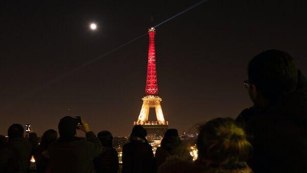 Эйфелева башня в Париже, подсвеченная в цвета бельгийского флага в знак солидарности с народом Бельгии после терактов в Брюсселе