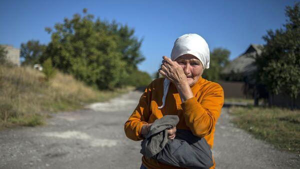 Местная жительница наблюдает за проходом колонны машин 38-го гуманитарного конвоя в Донецкой области. Архивное фото