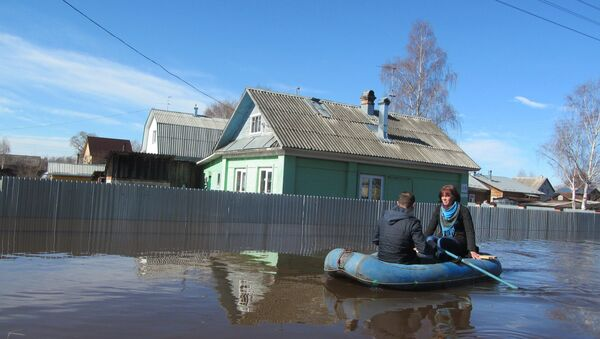 Люди на резиновой лодке во время паводка. Архивное фото