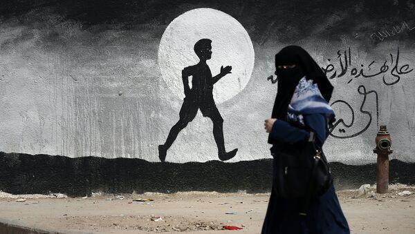 Жительница проходит мимо граффити на стене школы ООН в секторе Газа, Палестина. Архивное фото
