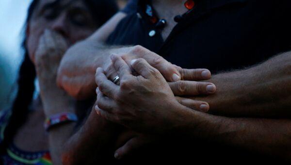 Люди держатся за руки после стрельбы в гей-клубе в Орландо. Архивное фото