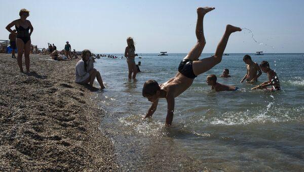 Отдыхающие на пляже Черного моря у детского оздоровительного лагеря Голубая волна. Архивное фото