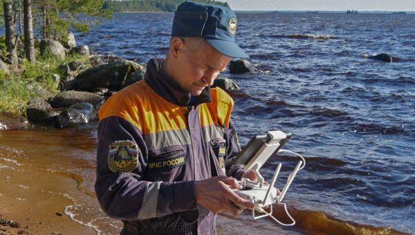 Сотрудник МЧС России обследует береговую линию при помощи беспилотного летательного аппарата во время поисково-спасательных работ на озере Сямозеро в Карелии