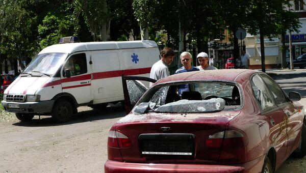 Мужчины у автомобиля, пострадавшего в результате взрыва на территории республиканского травматологического центра в Донецке