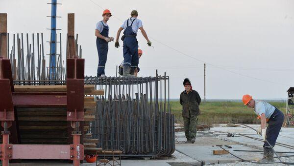Рабочие собирают опалубку под опору моста, строящегося через Керченский пролив в Крыму. 23 июня 2016