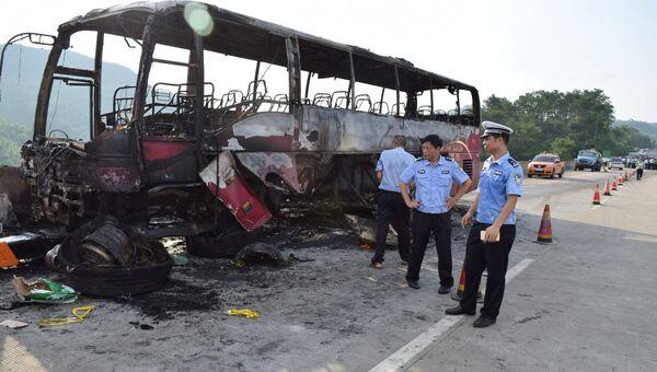 Полицейские рядом со сгоревшим автобусом в китайской провинции Хунань. 26 июня 2016 года