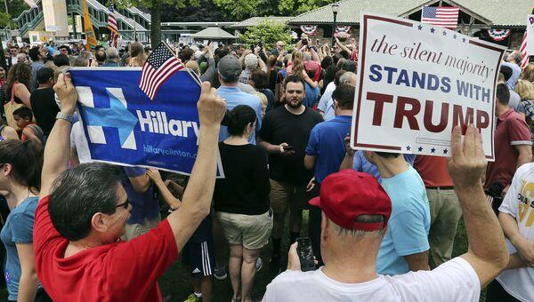 Избиратели с плакатами в поддержку кандидатов в президенты США Хиллари Клинтон и Дональда Трампа. 30 мая 2016 года. Архивное фото