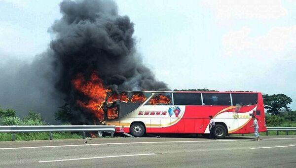 Полицейский и свидетель ДТП пытаются разбить окна горящего автобуса на Тайване