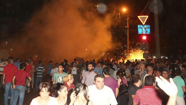 Протестующие во время столкновения с полицейскими на улице близ захваченного в Ереване здания полка патрульно-постовой службы