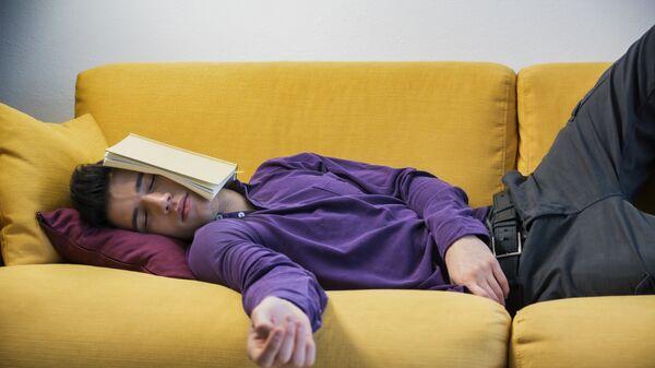 Мужчина отдыхает на диване с книгой