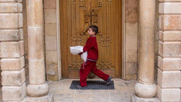 Мальчик с мешком гуманитарной помощи в Латакии. Архивное фото