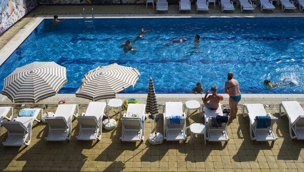 Отдыхающие у бассейна в семейном отеле. Архивное фото