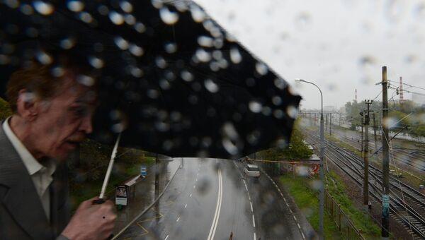 Мужчина во время дождя в Москве. Архивное фото