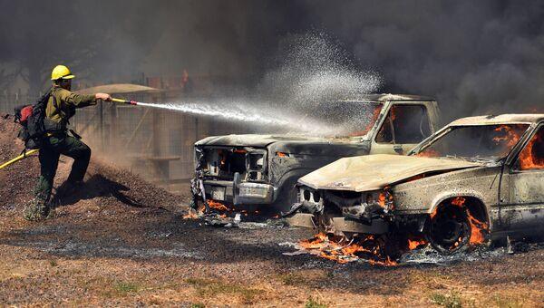 Пожарный тушит автомобили. Архивное фото