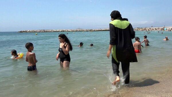 Девушка в буркини на пляже в Марселе, Франция