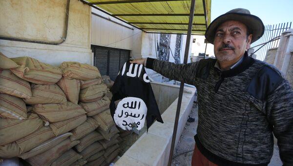 Житель Сирии держит флаг группировки Исламское государство. Архивное фото