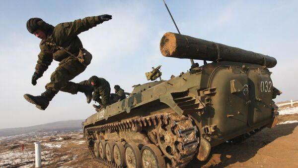 Военнослужащие экипажа БМП покидают машину после стрельбы во время учений мотострелковой бригады на полигоне в Приморском крае