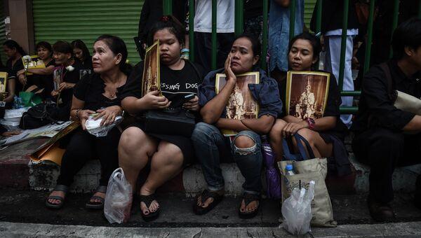 Женщины с портретами короля Таиланда Пхумипона Адульядета. Бангкок, Таиланд. Архивное фото