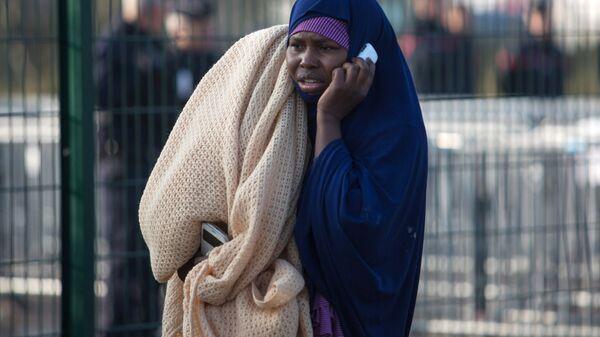 Беженка в специально организованном центре по распределению мигрантов рядом с лагерем Джунгли в Кале во Франции