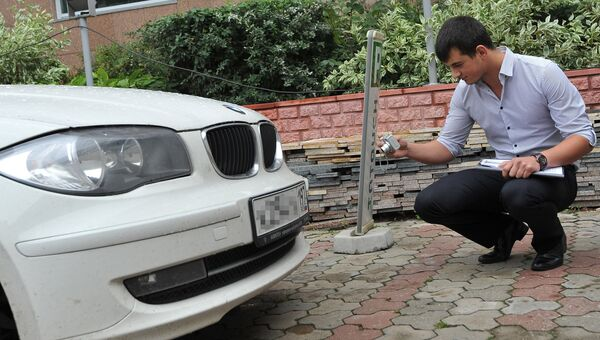 Сотрудник страховой компании проводит осмотр автомобиля. Архивное фото