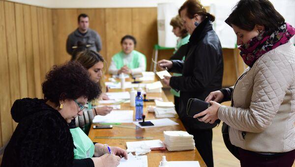 Избиратели голосуют во время второго тура парламентских выборов на одном из избирательных участков в Тбилиси